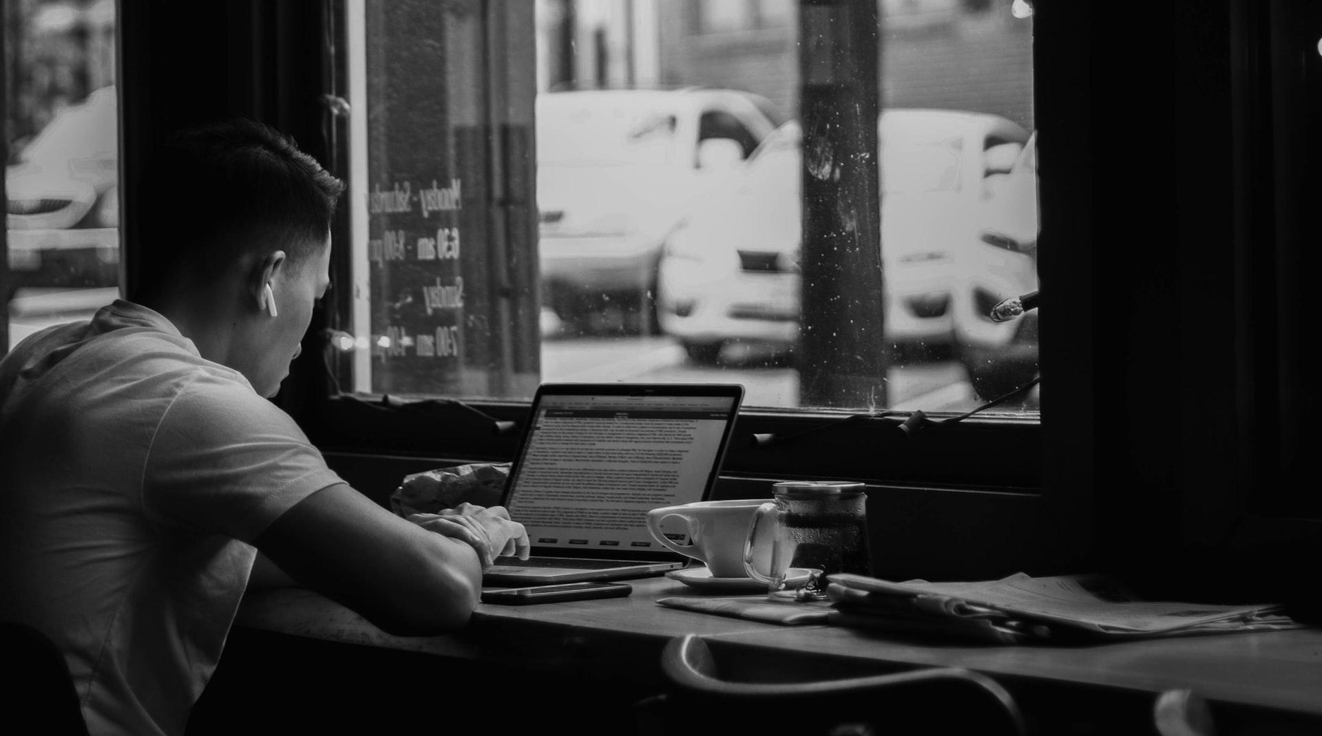 一人でカフェでプログラミングを勉強する青年