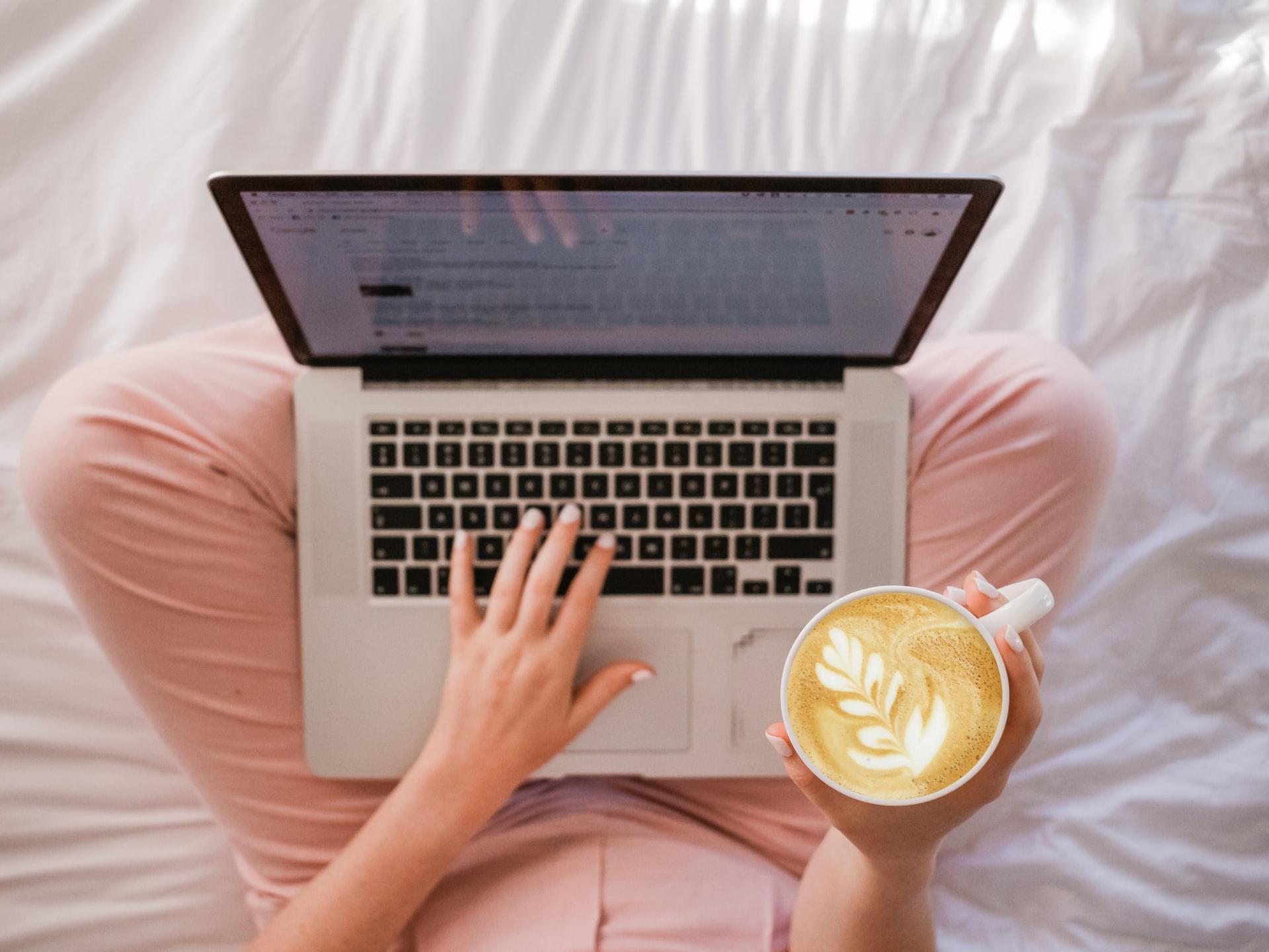ベッドの上でプログラミングをする人