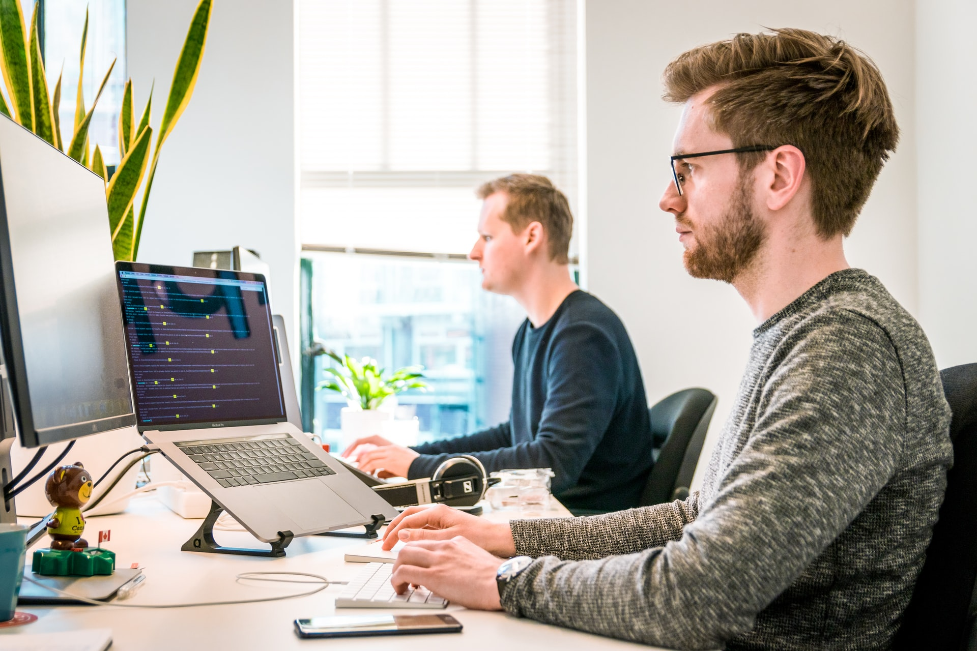 会社のデスクで黙々と作業する二人のプログラマー