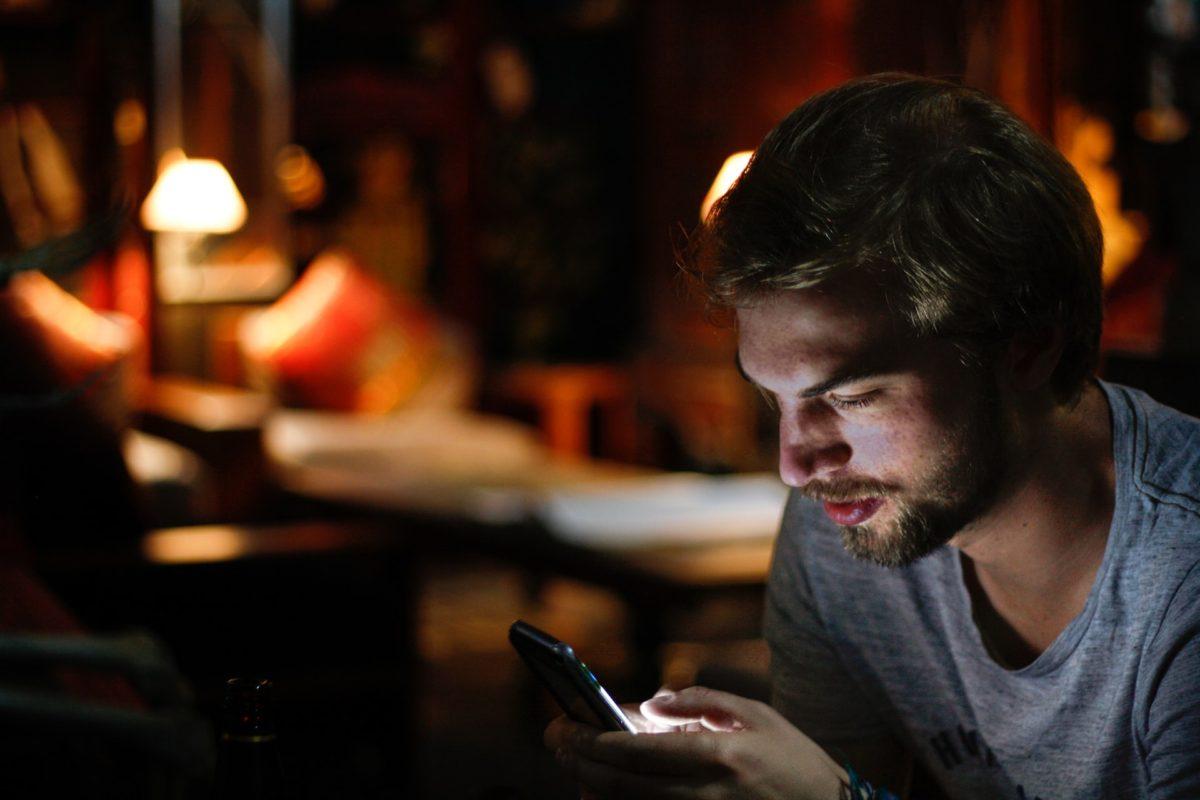 暗闇でスマートフォンを見る人