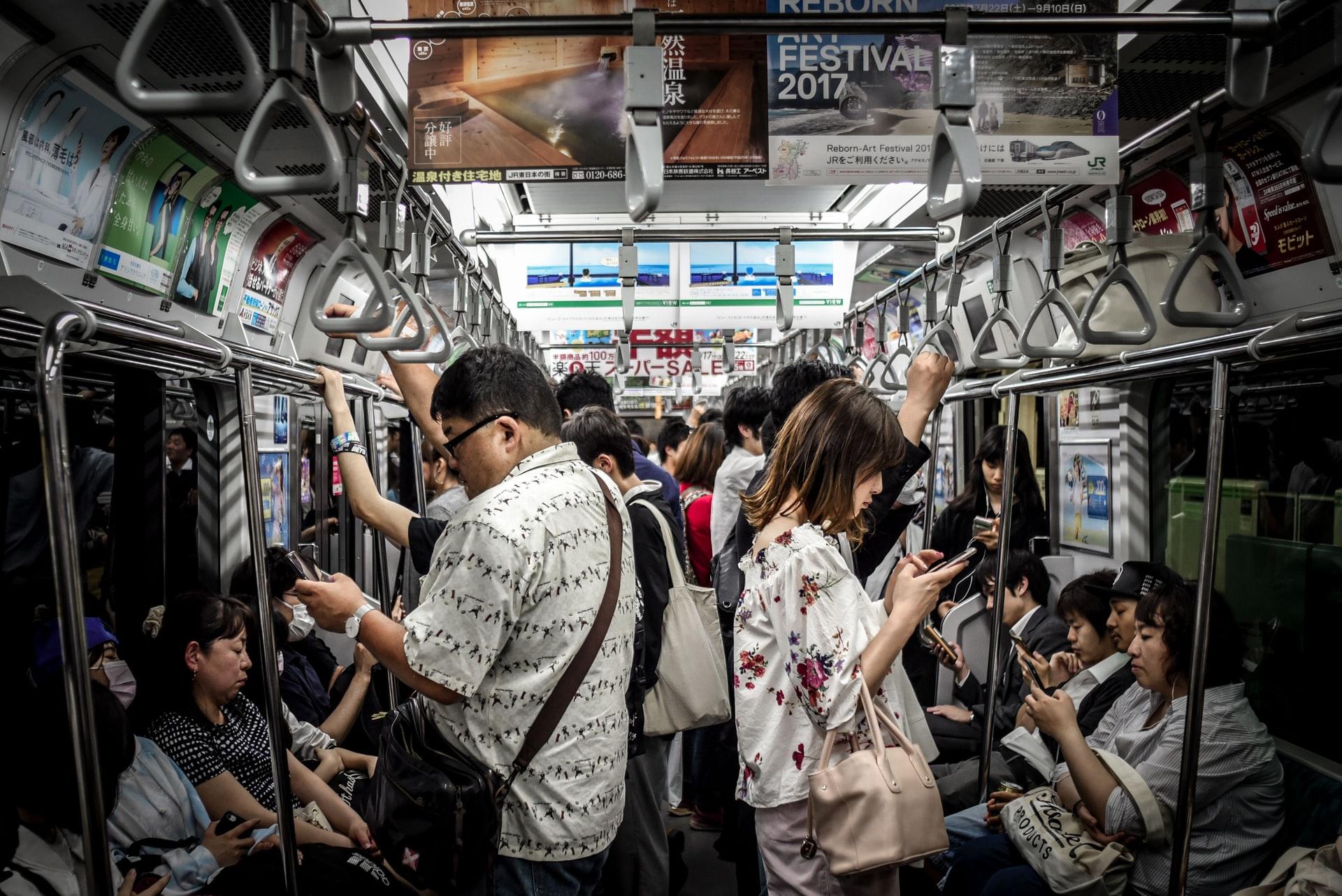 電車内でスマホを見る人たち