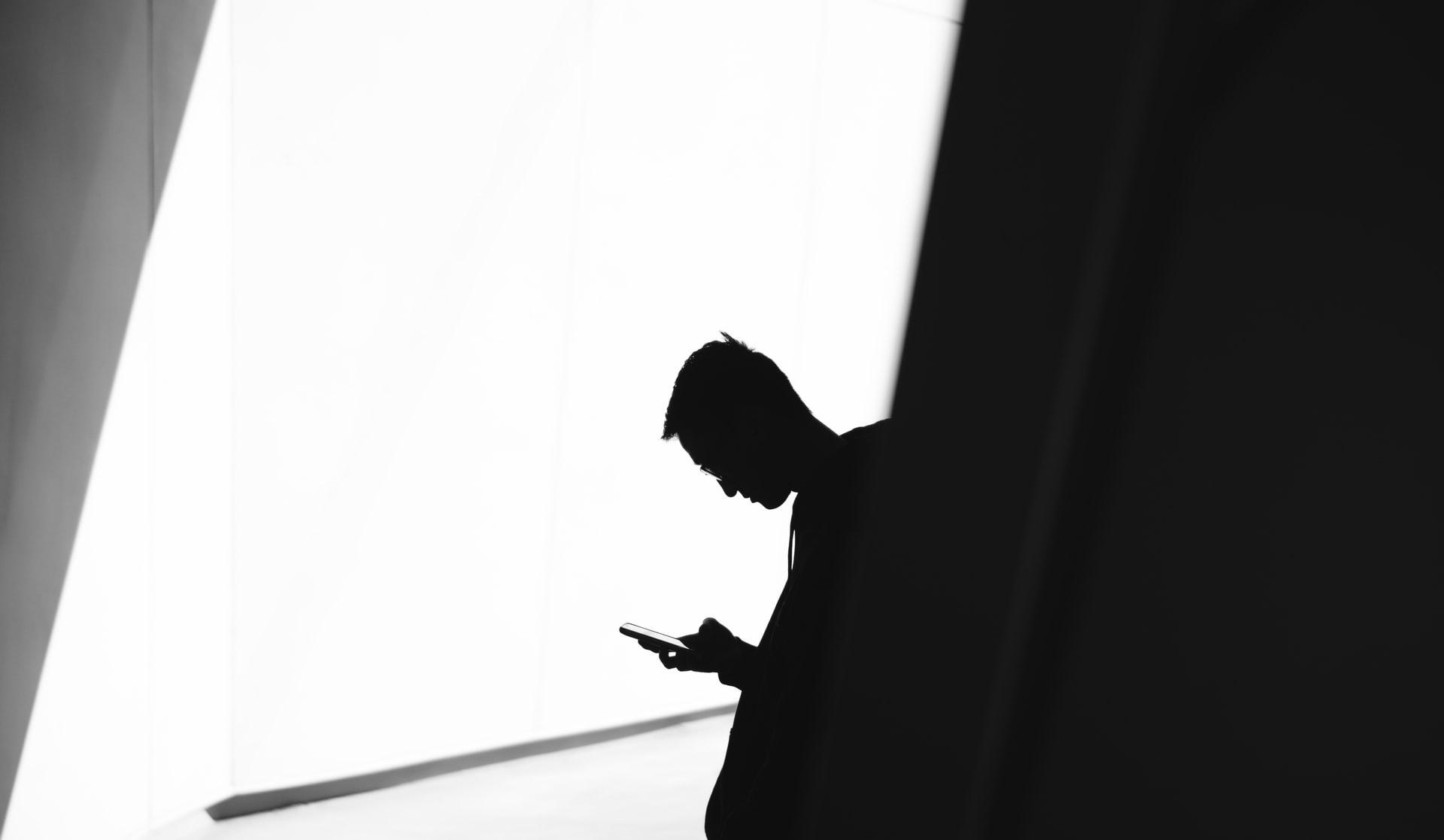 孤立してスマートフォンを閲覧する男性